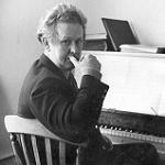 Ron Grainer seated at a piano