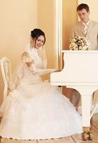 bride playing a white piano with groom standing beside her