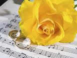 wedding rings and a yellow rose resting on sheet music